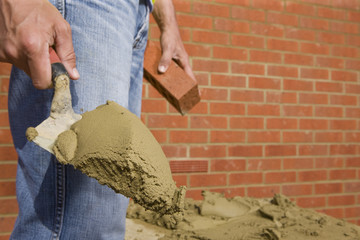 Close up of bricklayer holding mortar on trowel in front of brick wall