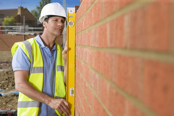 Bricklayer holding level tool against brick wall