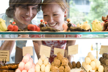 Couple looking at food on display in bakery, view through glass