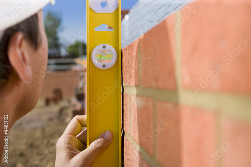 Close up of bricklayer holding level tool against brick wall