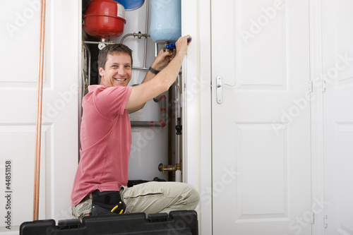 Portrait of smiling handyman fixing boiler in closet