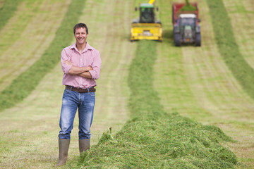 Portrait of smiling farmer in hay field with tractors