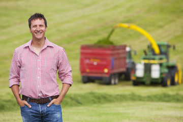 Portrait of smiling farmer in field with tractors
