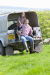 Portrait of shepherd and daughter with dogs on tailgate of truck in field