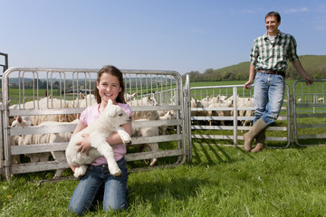 Portrait of shepherd and daughter holding lamb in pasture