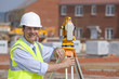 Portrait of smiling surveyor leaning on theodolite at construction site