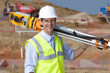 Portrait of smiling surveyor carrying theodolite at construction site