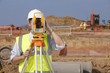 Surveyor looking through theodolite at construction site