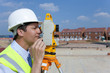 Close up profile of surveyor looking through theodolite at construction site