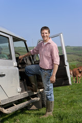 Portrait of smiling farmer leaning on truck in field