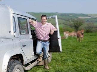 Portrait of smiling farmer leaning on truck in field
