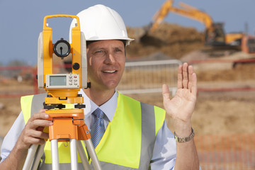 Close up of surveyor gesturing behind theodolite at construction site