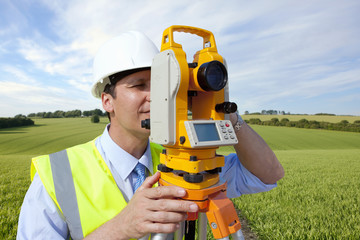 Close up of surveyor looking through theodolite in rural field