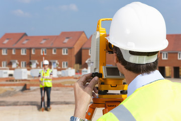Surveyor looking towards co-worker through theodolite at construction site