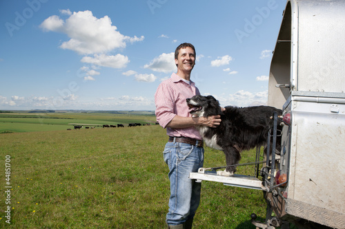 Portrait of smiling farmer petting dog on tailgate of truck in field