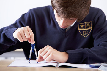 Close up of male student in school uniform using drawing compass at desk