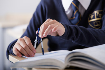 Close up of male student in school uniform using drawing compass at desk in classroom