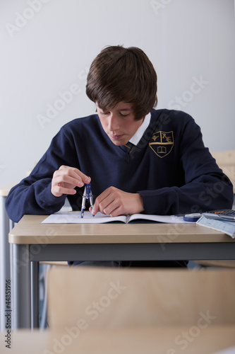 Male student in school uniform using drawing compass at desk in classroom