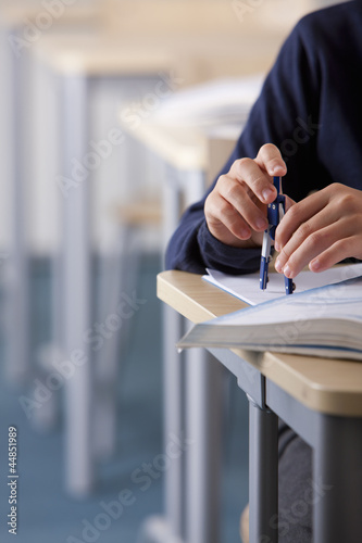 Close up of male student using drawing compass at desk in classroom