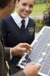 Portrait of smiling female student holding solar panel with teacher