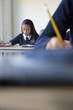 Students in school uniforms taking exam at desk in classroom