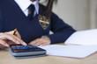 Female student in school uniform using calculator for exam at desk in classroom