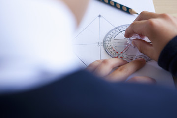 Male student using protractor at desk