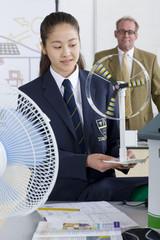 Teacher in background watching female student in school uniform with wind turbine model in science class