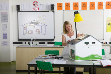 Female teacher adjusting solar panels on house model in science class
