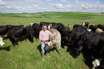 Portrait of smiling farmer feeding cattle in rural field