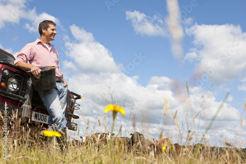 Smiling farmer with bucket leaning on truck in sunny rural field