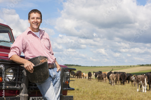 Portrait of smiling farmer with bucket leaning on truck in sunny rural field with grazing cattle herd