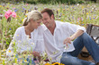 Smiling couple drinking white wine and picnicking in sunny wildflower field