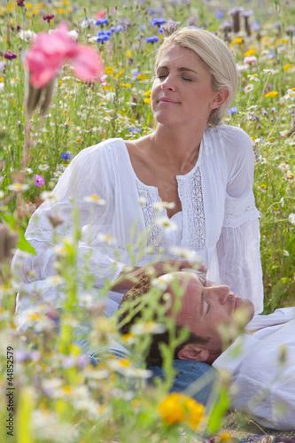 Man laying in womanճ lap in sunny wildflower field