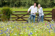 Couple with bicycles pointing in wildflower field