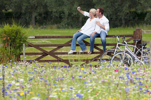 Couple taking self-portrait on fence in wildflower field