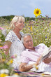 Senior man laying with wife and reading book in field of wildflowers