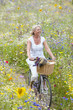 Smiling woman riding bicycle on path through field of wildflowers