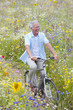 Smiling senior man riding bicycle on path through field of wildflowers