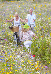 Senior couple standing with bicycles on path through wildflowers in field greeting granddaughter