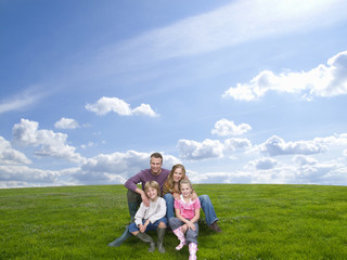 Family sitting together on grass in field