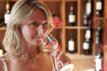 Woman smelling white wine in wine shop