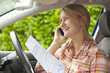 Smiling woman in car holding certificate and talking on cell phone