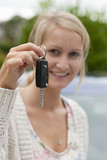 Excited woman holding keys to new car