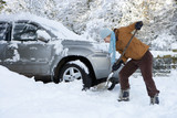Woman shoveling snow near car