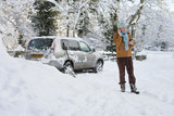 Woman standing in snow near car talking on cell phone
