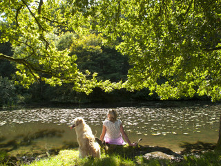 Serene woman relaxing on riverbank with dog