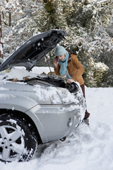 Woman standing in snow checking underneath carճ hood and talking on cell phone