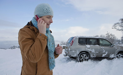 Woman standing in snow with skidded car talking on cell phone