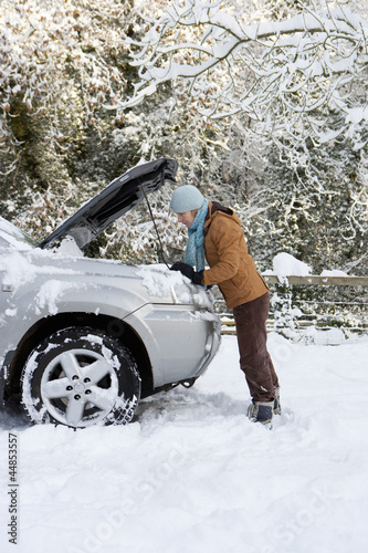 Woman standing in snow checking underneath carճ hood